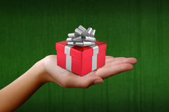 Person holding a red gift box. Hand of a person holding a red gift box with silver ribbons and bow Stock Photography
