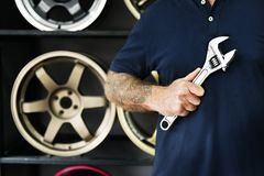 Person Holding Silver Crescent Wrench Behind Vehicle Wheels stock photos