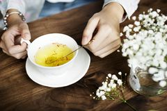 Person Holding Silver Spoon on White Ceramic Teacup With Yellow Liquid Inside Stock Images