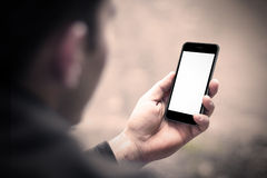 Person holding a smartphone with blank screen. Perspective from behind the arm Royalty Free Stock Photo