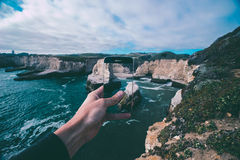 Person Holding Smartphone Capturing Pictures of Body of Water Beside Rock Formations Under Cloudy Sky during Daytime Royalty Free Stock Photography