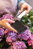 Person holding smartphone and credit card while standing in flower shop Royalty Free Stock Images