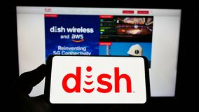 Person holding smartphone with logo of US television company DISH Network Corporation on screen in front of website.
