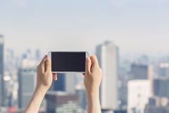 Person holding a smartphone on a urban background. Person holding a smartphone up high above a large city Stock Photography
