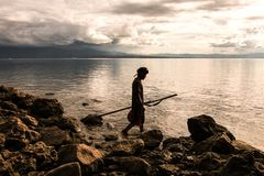 Person Holding Spear Beside Body of Water Royalty Free Stock Photography