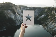 Person Holding Star Cutout Paper Facing Mountain Stock Image