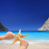 Person holding a starfish on a sandy beach Stock Images