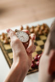 Person Holding Stop Watch Above Chess Board. Close Up Rear View of Unidentifiable Person Holding Stop Watch in Hand Above Chess Board Set for Game Out of Focus stock images