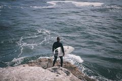 Person Holding Surfing Board Standing Cliff Beside Sea Stock Photos