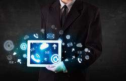 Person holding a tablet with blue technology icons and symbols. Person holding a white tablet with blue technology icons and symbols Royalty Free Stock Images