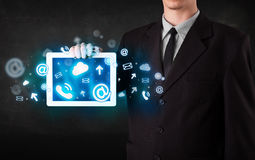 Person holding a tablet with blue technology icons and symbols Stock Images
