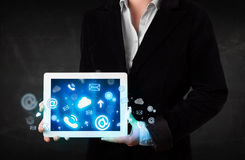 Person holding a tablet with blue technology icons and symbols. Person holding a white tablet with blue technology icons and symbols Stock Photos