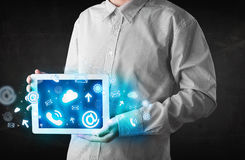 Person holding a tablet with blue technology icons and symbols. Person holding a white tablet with blue technology icons and symbols Royalty Free Stock Photography