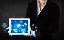 Person holding a tablet with blue technology icons and symbols. Person holding a white tablet with blue technology icons and symbols Royalty Free Stock Image