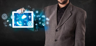 Person holding a tablet with blue technology icons and symbols. Person holding a white tablet with blue technology icons and symbols Royalty Free Stock Photos