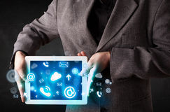 Person holding a tablet with blue technology icons. Person holding a white tablet with blue technology icons and symbols Royalty Free Stock Images