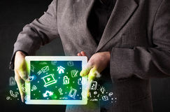 Person holding tablet with green media icons. Person holding tablet pc with green media icons and symbols Royalty Free Stock Images