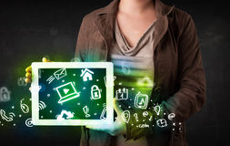 Person holding tablet with green media icons. Person holding tablet pc with green media icons and symbols Royalty Free Stock Photography