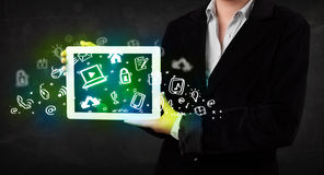 Person holding tablet with green media icons and symbols Stock Image