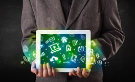Person holding tablet with green media icons and symbols. Person holding tablet pc with green media icons and symbols Stock Photos