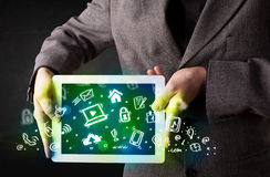 Person holding tablet with green media icons and symbols Royalty Free Stock Photo