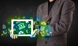 Person holding tablet with green media icons and symbols Stock Images