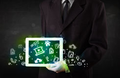 Person holding tablet with green media icons and symbols. Person holding tablet pc with green media icons and symbols Royalty Free Stock Images