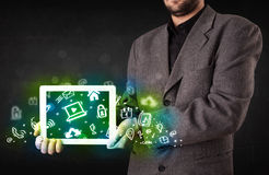 Person holding tablet with green media icons and symbols. Person holding tablet pc with green media icons and symbols Royalty Free Stock Image