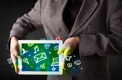 Person holding a tablet with media icons and symbols. Person holding a white tablet with media icons and symbols Stock Images