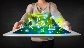 Person holding a tablet with media icons and symbols. Person holding a white tablet with media icons and symbols Royalty Free Stock Photo