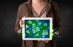 Person holding a tablet with media icons and symbols. Person holding a white tablet with media icons and symbols Stock Photography