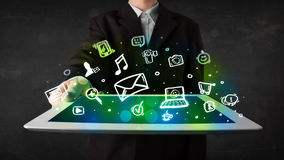 Person holding a tablet with media icons and symbols. Person holding a white tablet with media icons and symbols Stock Photos