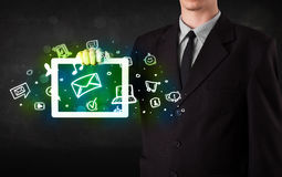 Person holding a tablet with media icons and symbols. Person holding a white tablet with media icons and symbols Royalty Free Stock Image
