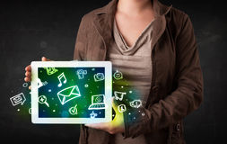 Person holding a tablet with media icons and symbols Royalty Free Stock Image