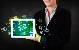 Person holding a tablet with media icons and symbols Royalty Free Stock Photo