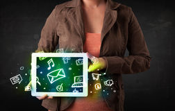 Person holding a tablet with media icons and symbols. Person holding a white tablet with media icons and symbols Stock Photo