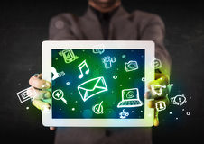 Person holding a tablet with media icons and symbols. Person holding a white tablet with media icons and symbols Stock Image