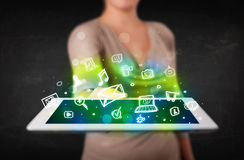 Person holding a tablet with media icons and symbols Royalty Free Stock Photos