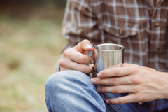 A person holding a titanium cup of tea Stock Photo