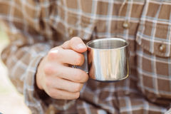 A person holding a titanium cup of tea Stock Photography