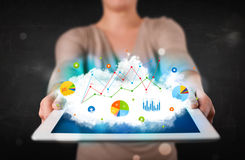 Person holding a touchpad with cloud technology and charts Stock Image