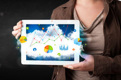 Person holding a touchpad with cloud technology and charts Royalty Free Stock Photo