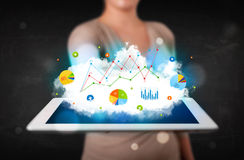 Person holding a touchpad with cloud technology and charts Stock Photo