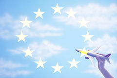 Person holding a toy plane flying in from of EU Flag.  stock photo