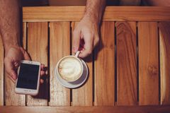 Person Holding Turned Off Gold Iphone 6 With Case and White Ceramic Cup Filled With Latte Royalty Free Stock Photos