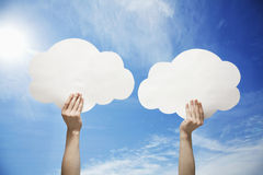 Person holding two cut out paper clouds against a blue sky with clouds Royalty Free Stock Images