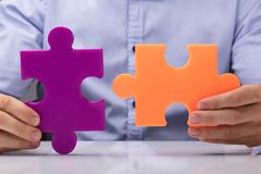 Person Holding Two Jigsaw Puzzle Images stock