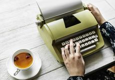 Person Holding Type Writer Beside Teacup and Saucer on Table stock image