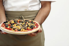 Person holding the uncooked pizza Stock Photo