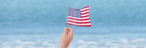 Person holding USA flag against sea background. Digital composite of Person holding USA flag against sea background Stock Photo